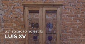parede rústica de tijolos ao fundo. na frente, cristaleira de madeira com vidros nas portas e taças no interior. Texto na imagem: Sofisticação no estilo Luís XV